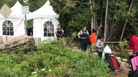 Asylum seekers cross over a narrow ditch from the United States to Canada.