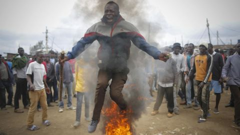 A supporter of the opposition leader Odinga, who leads the National Super Alliance coalition, jumps over a burning tire as he and others protest in Kibera.