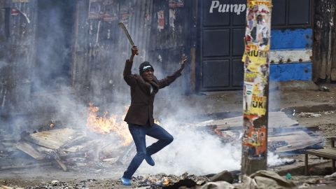 A man brandishing a machete challenges police next to a burning barricade during clashes between police and protesters in the Mathare slum of Nairobi.