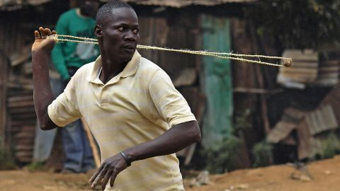 A protester throws a stone during clashes with riot police in the Kibera slum in Nairobi.