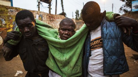 An injured man is carried in the Kibera slum of Nairobi.
