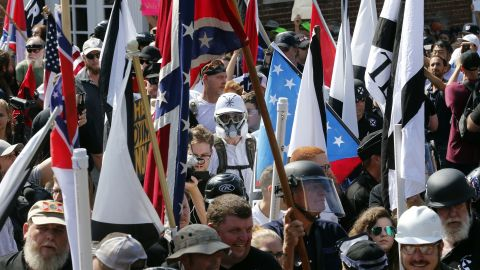 White nationalist demonstrators walk into the entrance of Lee Park surrounded by counter demonstrators in Charlottesville, Va., Saturday, Aug. 12, 2017. Gov. Terry McAuliffe declared a state of emergency and police dressed in riot gear ordered people to disperse after chaotic violent clashes between white nationalists and counter protestors.