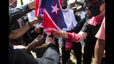 Counterprotesters try to burn a Confederate battle flag taken from white nationalist protesters.