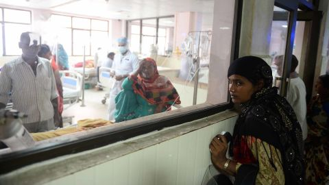 Indian relatives of patients wait outside the encephalitis ward at the Baba Raghav Das Hospital in Gorakhpur on August 14.