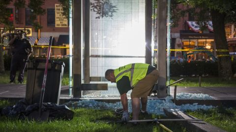 A worker cleans up broken glass at the New England Holocaust Memorial that was vandalized Monday.