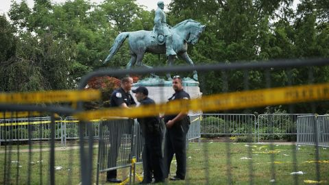 Police stand watch near the statue of Confederate Gen. Robert E. Lee in the center of Emancipation Park in Charlottesville