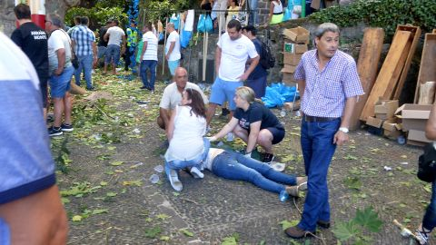 People help the injured after a falling tree killed 13 people on August 15, 2017, in Madeira, Portugal.