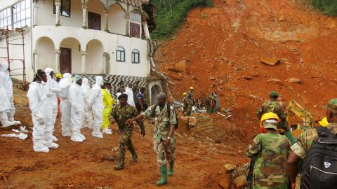 Search-and-rescue team members and soldiers by the site of the mudslide.