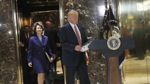 President Donald Trump, followed by Transportation Secretary Elaine Chao, arrives to speaks to the media in the lobby of Trump Tower in New York, Tuesday, Aug. 15, 2017. (AP Photo/Pablo Martinez Monsivais)