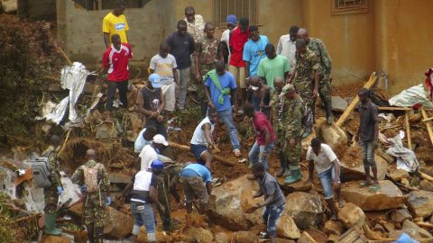 Volunteers search for bodies at the scene of the mudslide, which was caused by heavy rains.