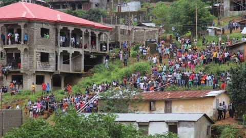 Residents look on as workers remove wreckage from the Regent area of Freetown, after landslides struck the capital of the west African state on Monday.