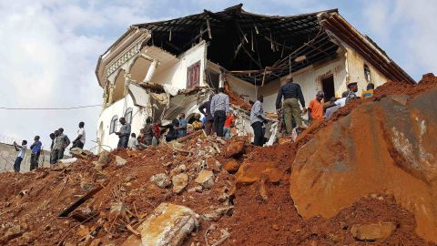 People inspect the damage at the mudslide site on Tuesday afternoon. Sierra Leone's President Ernest Bai Koroma has declared seven days of mourning across the country, with immediate effect.