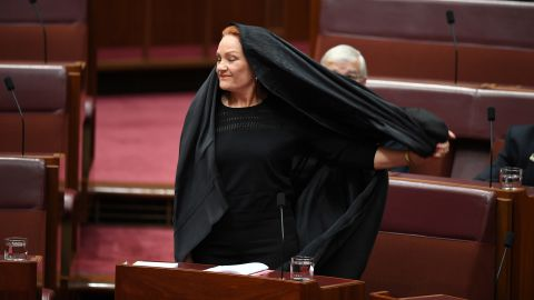 Hanson takes off her burqa veil during Senate Question Time at Parliament House in Canberra.