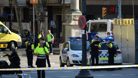 """Medical staff members and policemen stand in a cordoned off area after a van ploughed into the crowd, injuring several persons on the Rambla in Barcelona on August 17, 2017. Police in Barcelona said they were dealing with a """"terrorist attack"""" after a vehicle ploughed into a crowd of pedestrians on the city's famous Las Ramblas boulevard on August 17, 2017. Police were clearing the area after the incident, which has left a number of people injured. / AFP PHOTO / Josep LAGO        (Photo credit should read JOSEP LAGO/AFP/Getty Images)"""