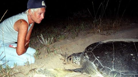 Mona Khalil, a Lebanese ecologist, activist looks at a turtle at a coast in the southern Lebanese port city of Tyre in 2002.