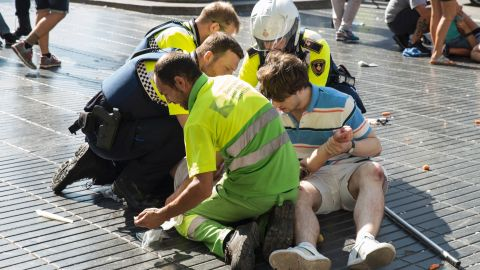 """A person is helped by Spanish policemen and two men after a van ploughed into the crowd, killing at least 13 people and injuring around 100 others on the Rambla in Barcelona on August 17, 2017. A driver deliberately rammed a van into a crowd on Barcelona's most popular street on August 17, 2017 killing at least 13 people before fleeing to a nearby bar, police said.  Officers in Spain's second-largest city said the ramming on Las Ramblas was a """"terrorist attack"""". The driver of a van that mowed into a packed street in Barcelona is still on the run, Spanish police said. / AFP PHOTO / Nicolas CARVALHO OCHOA        (Photo credit should read NICOLAS CARVALHO OCHOA/AFP/Getty Images)"""