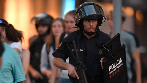 """Spanish policemen stand guard in a cordoned off area after a van ploughed into the crowd, killing 13 persons and injuring over 50 on the Rambla in Barcelona on August 17, 2017. A driver deliberately rammed a van into a crowd on Barcelona's most popular street on August 17, 2017 killing at least 13 people before fleeing to a nearby bar, police said.  Officers in Spain's second-largest city said the ramming on Las Ramblas was a """"terrorist attack"""" and a police source said one suspect had left the scene and was """"holed up in a bar"""". The police source said they were hunting for a total of two suspects. / AFP PHOTO / LLUIS GENE        (Photo credit should read LLUIS GENE/AFP/Getty Images)"""