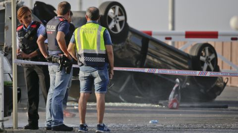 Police officers stand near an overturned car onto a platform at the spot where terrorists were intercepted by police in Cambrils, Friday, Aug. 18.