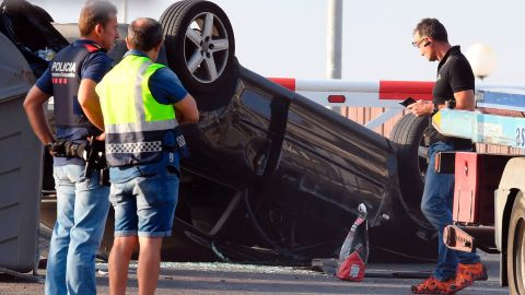 Police officers investigate a car in Cambrils.