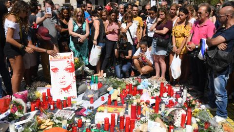 People stand next to flowers, candles and other items set up on the Las Ramblas boulevard in Barcelona as they pay tribute to the victims of the Barcelona attack, a day after a van ploughed into the crowd, killing 13 persons and injuring over 100 on August 18, 2017.  Police hunted for the driver who rammed a van into pedestrians on an avenue crowded with tourists in Barcelona, leaving 13 people dead and  more than 100 injured, just hours before a second assault in a resort along the coast. / AFP PHOTO / PASCAL GUYOT        (Photo credit should read PASCAL GUYOT/AFP/Getty Images)