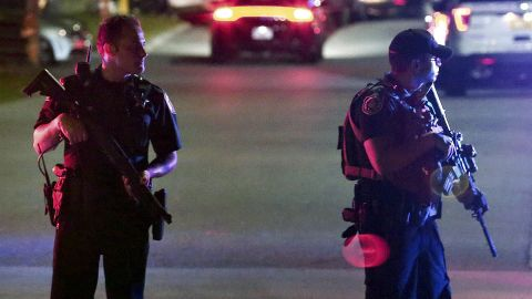 Two law enforcement officers stand guard outside Osceola Regional Medical Center after two Kissimmee police officers were shot Friday, August 18, 2017, in Kissimmee, Florida. Police said one officer was killed and another gravely injured.