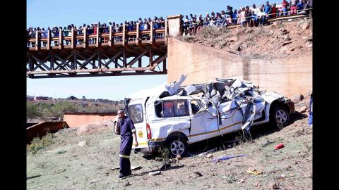 Residents watch from a bridge as authorities investigate a deadly minibus crash near Pietermaritzburg, South Africa.