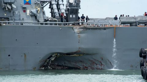 """Damage to the portside is visible as the Guided-missile destroyer USS John S. McCain (DDG 56) steers towards Changi naval base in Singapore following a collision with the merchant vessel Alnic MC Monday, Aug. 21, 2017. The USS John S. McCain was docked at Singapore's naval base with """"significant damage"""" to its hull after an early morning collision with the Alnic MC as vessels from several nations searched Monday for missing U.S. sailors."""