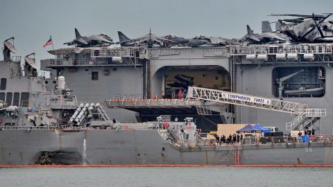"""The guided-missile destroyer USS John S. McCain (foreground), seen with a hole on its portside after a collision with a tanker, docks next to the USS America (behind) at Changi naval base in Singapore on August 22, 2017.The US Navy announced a fleet-wide global investigation after the latest in a series of warship accidents left 10 sailors missing and five injured. Chief of Naval Operations Admiral John Richardson ordered commanders within a week to set aside time, perhaps """"one or two days"""", for crews to sit down together after the destroyer USS John S. McCain collided with a tanker off Singapore early on August 21. / AFP PHOTO / Roslan RAHMAN        (Photo credit should read ROSLAN RAHMAN/AFP/Getty Images)"""