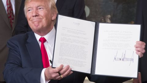 WASHINGTON, D.C. - AUGUST 14: (AFP-OUT) U.S. President Donald J. Trump holds a memorandum he just signed on addressing China's laws, policies, practices, and actions related to intellectual property, innovation, and technology at The White House on August 14, 2017 in Washington, DC.  (Photo by Chris Kleponis-Pool/Getty Images)