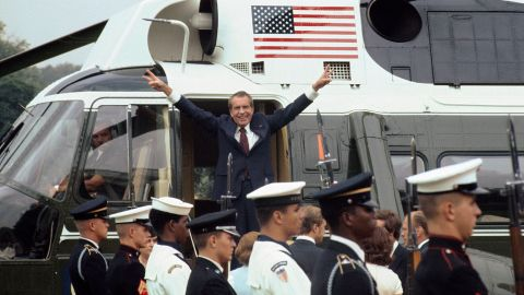 As he boards the White House helicopter after resigning the presidency, Richard M. Nixon smiles and gives the victory sign.