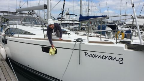 """Kellie gives their boat, """"Boomerang"""", a good polish before its maiden voyage."""