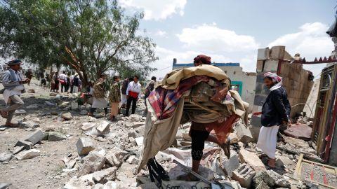 A Yemeni man carries his belongings after an airstrike heavily damaged his neighborhood.