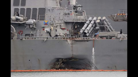 The damaged port aft hull of the USS John S. McCain, is visible while docked at Singapore's Changi naval base on Tuesday, Aug. 22.