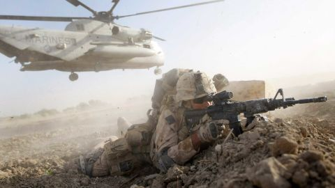 MAIN POSHTEH, AFGHANISTAN - JULY 02:  A U.S. Marine from 2nd Marine Expeditionary Brigade, RCT 2nd Battalion 8th Marines Echo Co. takes up a fighting position after off loading from a helicopter during the start of Operation Khanjari on July 2, 2009 in Main Poshteh, Afghanistan. The Marines are part of an operation to take areas in the Southern Helmand Province that Taliban fighters are using as a resupply route and to help the local Afghan population prepare for the upcoming presidential elections.  (Photo by Joe Raedle/Getty Images)