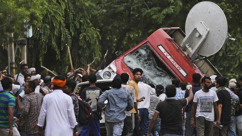 Followers of Gurmeet Ram Rahim Singh overturn a satellite van Friday in Panchkula, India.