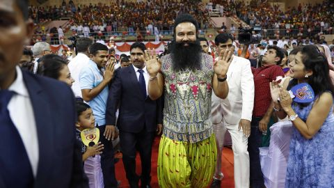 """FILE- In this Oct. 5, 2016 file photo, Indian spiritual guru who calls himself Saint Dr. Gurmeet Ram Rahim Singh Ji Insan, center, greets followers as he arrives for a press conference ahead of the release of his new movie """"MSG, The Warrior Lion Heart,"""" in New Delhi, India. Several cities in north India were under a security lock down Thursday ahead of a verdict in a rape trial involving a controversial and hugely popular spiritual leader. (AP Photo/Tsering Topgyal, File)"""