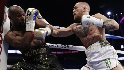 McGregor swarms Mayweather at the start of the fight.