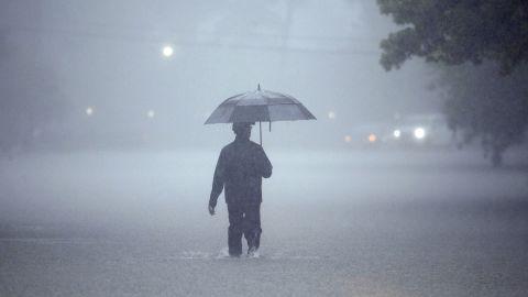 A man walks through deep water on Sunday in Houston.
