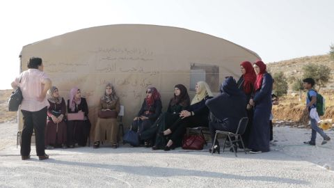 Mothers and teachers sit outside the tent in Jub El-Thib.