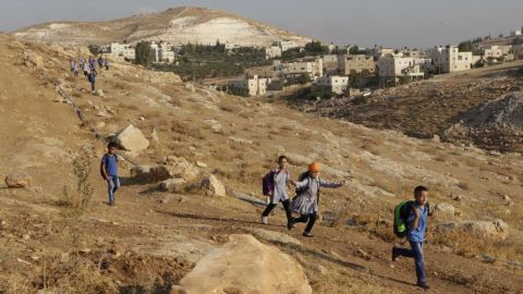 Children in their school uniforms run towards school.
