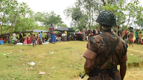 A Bangladeshi border guard soldier stands guard near a Rohingya refugee shelter, yards inside the border, in Cox's Bazar.