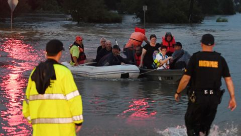 People are rescued from a hotel by boat after Hurricane Harvey caused heavy flooding in Houston, Texas on August 27, 2017.  Massive flooding unleashed by deadly monster storm Harvey left Houston -- the fourth-largest city in the United States -- increasingly isolated as its airports and highways shut down and residents fled homes waist-deep in water. / AFP PHOTO / MARK RALSTON        (Photo credit should read MARK RALSTON/AFP/Getty Images)