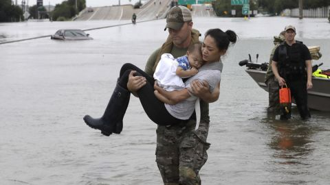 CORRECTS FROM CONNIE TO CATHERINE - Houston Police SWAT officer Daryl Hudeck carries Catherine Pham and her 13-month-old son Aiden after rescuing them from their home surrounded by floodwaters from Tropical Storm Harvey Sunday, Aug. 27, 2017, in Houston. The remnants of Hurricane Harvey sent devastating floods pouring into Houston Sunday as rising water chased thousands of people to rooftops or higher ground. (AP Photo/David J. Phillip)