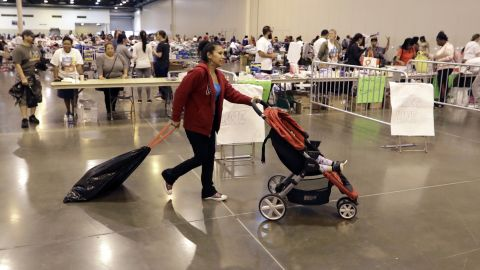 Narcedalia Osorio pushes her son Noel through a shelter set up inside NRG Center Wednesday, August 30, 2017, in Houston.