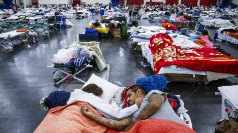Tammy Dominguez and her husband, Christopher, sleep on cots at the George R. Brown Convention Center, where thousands of people were taking shelter in Houston.