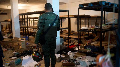 A Venezuelan National Guard member surveys debris in a looted supermarket in December 2016.
