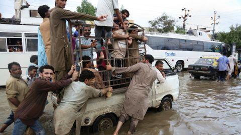 People push a vehicle after heavy rainfall in Karachi, Pakistan, Thursday, Aug. 31, 2017.