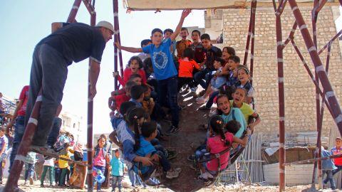 Syrian children ride an attraction in the northwestern Syrian city of Idlib during Eid holidays last year.