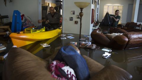 Larry Koser Jr. and his son Matthew look for important papers and heirlooms inside a flooded home in Houston.