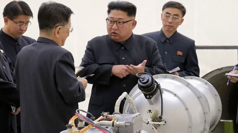 This undated picture released by North Korea's official Korean Central News Agency (KCNA) on September 3, 2017 shows North Korean leader Kim Jong Un, center, looking at a metal casing with two bulges at an undisclosed location.